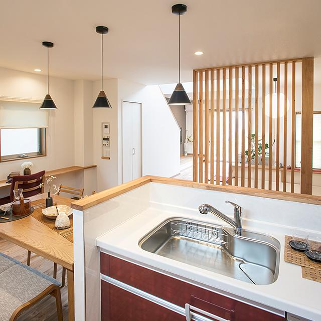 天然の無垢材を採用し縦格子が程よく仕切るキッチンとリビング